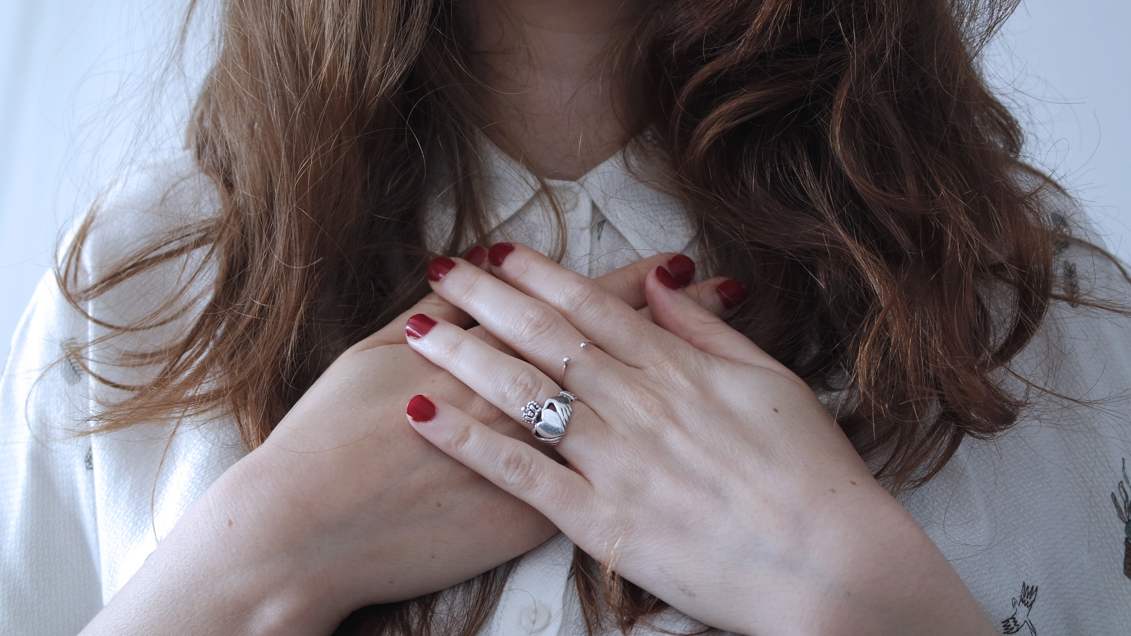 a person with long hair, red nails, and rings, holding their hands over the center of their chest